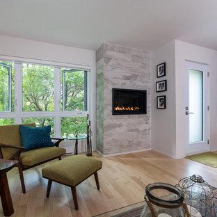 モントリオールの中サイズのミッドセンチュリースタイルのおしゃれなLDK (グレーの壁、淡色無垢フローリング、横長型暖炉、タイルの暖炉まわり、壁掛け型テレビ) の写真