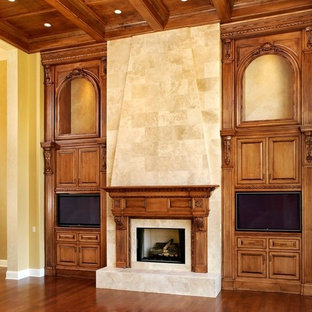 Photo of a large traditional living room in Cincinnati with white walls, dark hardwood floors, a standard fireplace, a stone fireplace surround and a built-in media wall.