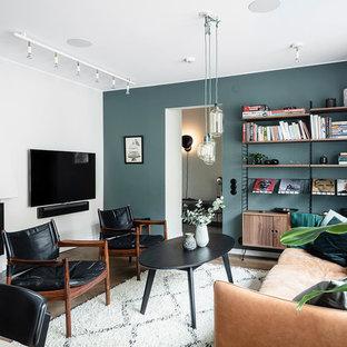 Inspiration för ett stort skandinaviskt allrum med öppen planlösning, med blå väggar, mörkt trägolv, en standard öppen spis, en spiselkrans i gips, en väggmonterad TV och brunt golv
