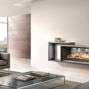 Modelo de salón para visitas abierto, moderno, grande, sin televisor, con paredes blancas, chimenea lineal, marco de chimenea de metal y suelo de baldosas de cerámica