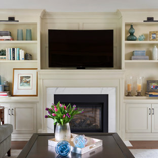 Mid-sized elegant medium tone wood floor and brown floor living room library photo in Toronto with beige walls, a standard fireplace, a stone fireplace and a wall-mounted tv