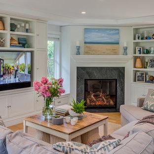 ボストンのビーチスタイルのおしゃれなリビング (グレーの壁、淡色無垢フローリング、コーナー設置型暖炉、タイルの暖炉まわり、埋込式メディアウォール、ベージュの床) の写真