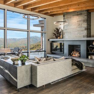 Bild på ett stort funkis allrum med öppen planlösning, med vita väggar, mellanmörkt trägolv, en standard öppen spis, en spiselkrans i metall, brunt golv och en väggmonterad TV