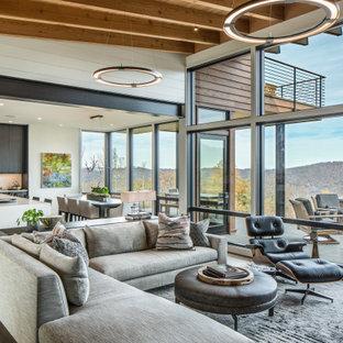 Modern inredning av ett mellanstort allrum med öppen planlösning, med vita väggar, mellanmörkt trägolv, en standard öppen spis, en spiselkrans i metall, en inbyggd mediavägg och brunt golv