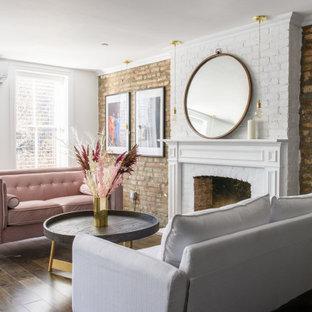 Immagine di un soggiorno chic aperto con pareti bianche, camino classico, cornice del camino in mattoni, pavimento marrone e pareti in mattoni
