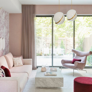 Foto de salón abierto, contemporáneo, grande, sin chimenea, con paredes rosas, televisor colgado en la pared, suelo de madera clara y suelo beige