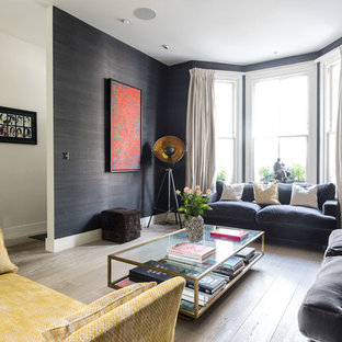 This is an example of a medium sized eclectic enclosed living room in London with black walls, light hardwood flooring and grey floors.