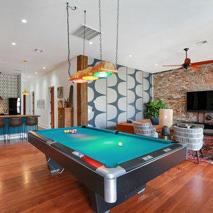 ニューオリンズのインダストリアルスタイルのおしゃれなLDK (白い壁、無垢フローリング、壁掛け型テレビ、茶色い床) の写真