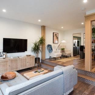 Foto de salón abierto, tradicional renovado, pequeño, con paredes blancas, suelo de madera en tonos medios, televisor colgado en la pared y suelo marrón