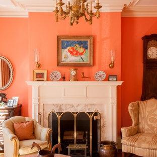 Diseño de salón para visitas tradicional con parades naranjas, suelo de madera en tonos medios, chimenea tradicional y marco de chimenea de piedra