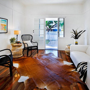 Mid-sized tropical living room in Townsville with white walls and medium hardwood floors.