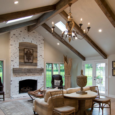 Inspiration for a large cottage formal and open concept medium tone wood floor and brown floor living room remodel in Kansas City with gray walls, a standard fireplace and a stone fireplace