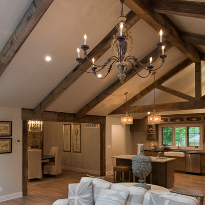 Large cottage formal and open concept medium tone wood floor and brown floor living room photo in Kansas City with gray walls, a standard fireplace and a stone fireplace
