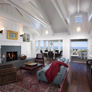Ispirazione per un grande soggiorno stile marino aperto con pareti bianche, camino classico, sala formale, parquet scuro, cornice del camino in cemento e nessuna TV