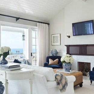 ロサンゼルスの中サイズのビーチスタイルのおしゃれなLDK (フォーマル、グレーの壁、カーペット敷き、標準型暖炉、木材の暖炉まわり、壁掛け型テレビ) の写真