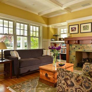 Idee per un soggiorno stile americano con pareti gialle, camino classico e cornice del camino piastrellata