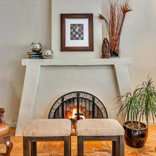 Esempio di un soggiorno american style di medie dimensioni e chiuso con sala formale, pareti beige, pavimento in terracotta, camino classico, cornice del camino in intonaco, nessuna TV e pavimento marrone