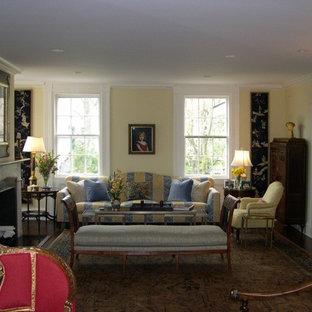 ニューヨークの大きいトラディショナルスタイルのおしゃれな独立型リビング (フォーマル、黄色い壁、標準型暖炉、石材の暖炉まわり、テレビなし、濃色無垢フローリング、茶色い床) の写真
