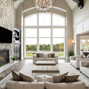 ミネアポリスの巨大なトラディショナルスタイルのおしゃれなLDK (無垢フローリング、標準型暖炉、石材の暖炉まわり、茶色い床、ベージュの壁) の写真