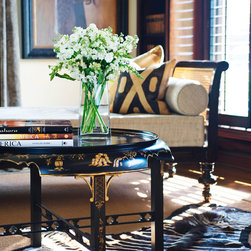 Edwards Residence - This library melds traditional and ethnic elements, incorporating African items from the client's travels. Serving as a library and music room, this space has a neutral and off white palette framed by dark wood moldings and trim and stained wooden shutters and a custom stained bookcase. The draperies are made of hand-painted taupe velvet, and the hardware is painted metallic silver with glass finials.