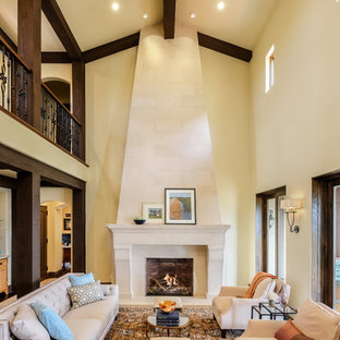 Inspiration for a mid-sized mediterranean formal loft-style living room in Sacramento with yellow walls, a standard fireplace, a stone fireplace surround, no tv and beige floor.