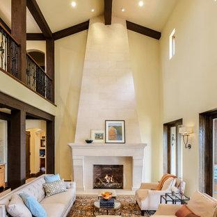 サクラメントの中くらいの地中海スタイルのおしゃれなリビングロフト (フォーマル、黄色い壁、標準型暖炉、石材の暖炉まわり、テレビなし、ベージュの床) の写真