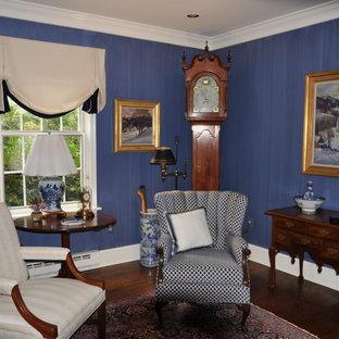 Esempio di un piccolo soggiorno chic chiuso con sala formale, pareti blu, parquet scuro, nessuna TV, pavimento marrone, camino classico e cornice del camino in pietra