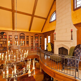 Living room library - mid-sized traditional loft-style medium tone wood floor living room library idea in Raleigh with yellow walls, a standard fireplace, a wood fireplace surround and no tv