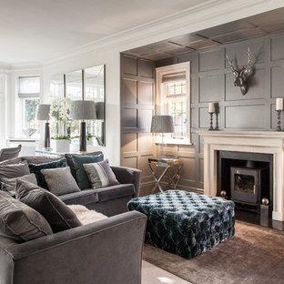 ハンプシャーの中サイズのトラディショナルスタイルのおしゃれなLDK (カーペット敷き、フォーマル、グレーの壁、薪ストーブ) の写真