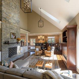 Imagen de salón abierto, clásico, con paredes marrones, suelo de madera oscura, chimenea tradicional, marco de chimenea de piedra y suelo marrón