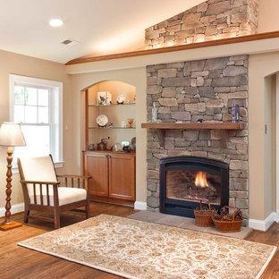 Foto de salón clásico con paredes beige, chimenea tradicional y marco de chimenea de piedra