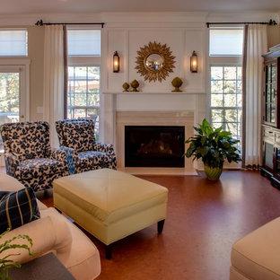 シャーロットの中サイズのトラディショナルスタイルのおしゃれなLDK (ベージュの壁、コルクフローリング、標準型暖炉、石材の暖炉まわり、据え置き型テレビ) の写真