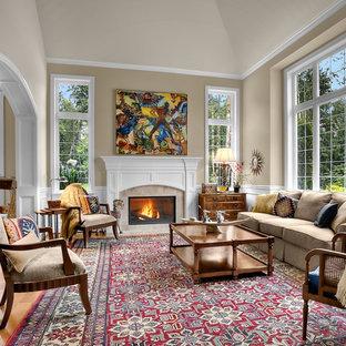 Diseño de salón tradicional, sin televisor, con paredes beige, suelo de madera en tonos medios y marco de chimenea de baldosas y/o azulejos