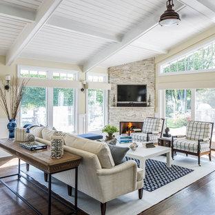 Modelo de salón para visitas abierto, clásico, de tamaño medio, con suelo de madera oscura, chimenea de esquina, marco de chimenea de piedra, televisor colgado en la pared y paredes beige