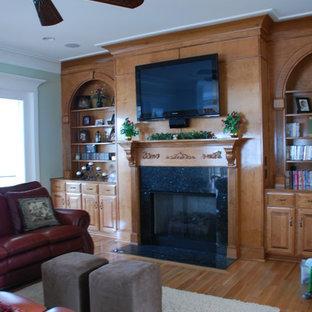 Foto di un grande soggiorno tradizionale aperto con sala formale, TV a parete, pareti verdi, parquet chiaro e cornice del camino in pietra