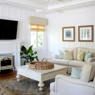 Inspiration for a traditional living room in Orange County with white walls, a wall-mounted tv and a wood stove.