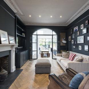 Inspiration för klassiska separata vardagsrum, med svarta väggar, mellanmörkt trägolv och en standard öppen spis