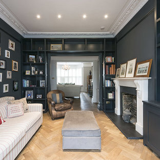 Design ideas for a traditional enclosed living room in London with black walls, light hardwood flooring, a standard fireplace and a wall mounted tv.
