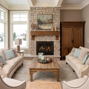 Imagen de salón para visitas clásico con paredes beige, suelo de madera en tonos medios, chimenea tradicional, marco de chimenea de piedra, televisor retractable y suelo azul
