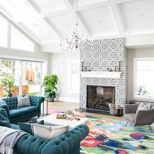 Transitional medium tone wood floor and brown floor living room photo in Orange County with gray walls, a standard fireplace and a tile fireplace