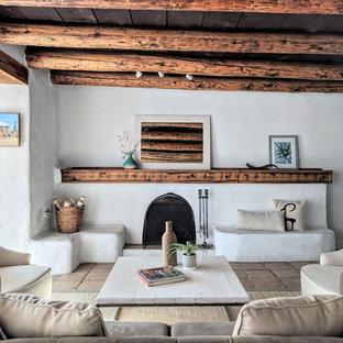 他の地域の中サイズのサンタフェスタイルのおしゃれな独立型リビング (白い壁、テラコッタタイルの床、標準型暖炉、コンクリートの暖炉まわり、テレビなし、ベージュの床) の写真