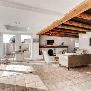 他の地域の中くらいのサンタフェスタイルのおしゃれな独立型リビング (白い壁、テラコッタタイルの床、標準型暖炉、コンクリートの暖炉まわり、テレビなし、ベージュの床) の写真