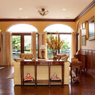 Diseño de salón para visitas abierto, tradicional, de tamaño medio, con paredes amarillas, suelo de madera oscura, chimenea tradicional y marco de chimenea de piedra