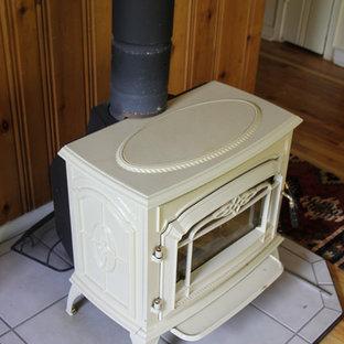 デンバーの小さいトラディショナルスタイルのおしゃれな独立型リビング (茶色い壁、淡色無垢フローリング、薪ストーブ、木材の暖炉まわり、茶色い床) の写真