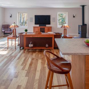 Ejemplo de salón abierto, minimalista, grande, con paredes rosas, suelo de madera en tonos medios, estufa de leña, televisor colgado en la pared y suelo beige