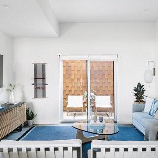 オースティンの中サイズのビーチスタイルのおしゃれなLDK (白い壁、コンクリートの床、グレーの床、フォーマル、暖炉なし、壁掛け型テレビ) の写真
