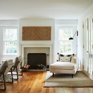Large trendy open concept light wood floor living room photo in New York with white walls, a standard fireplace, a stone fireplace and a wall-mounted tv
