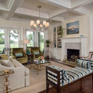 チャールストンの広いトランジショナルスタイルのおしゃれなLDK (濃色無垢フローリング、標準型暖炉、フォーマル、石材の暖炉まわり、茶色い床、黄色い壁、据え置き型テレビ) の写真
