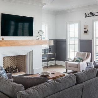 Foto di un grande soggiorno stile marinaro con pareti bianche, pavimento in legno massello medio, camino classico, cornice del camino in intonaco, TV a parete e pavimento marrone