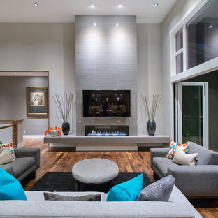 Ejemplo de salón minimalista, extra grande, con paredes grises, suelo de madera oscura y marco de chimenea de baldosas y/o azulejos